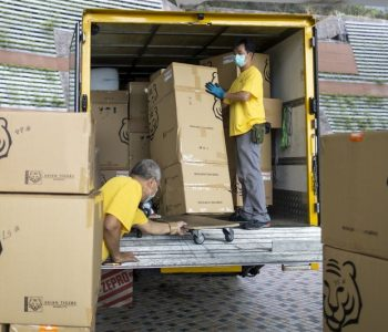 Movers load boxes into a truck during a customer's relocation process